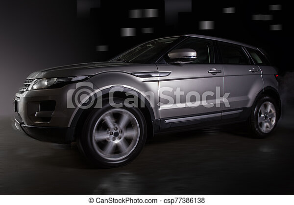 SUV moves at night on a city street - csp77386138