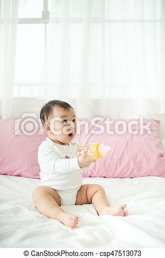 Sweet baby girl holding water bottle at home. - csp47513073