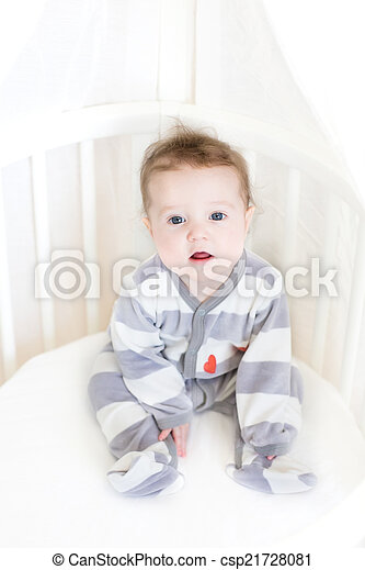 Sweet baby girl sitting in a white round crib - csp21728081