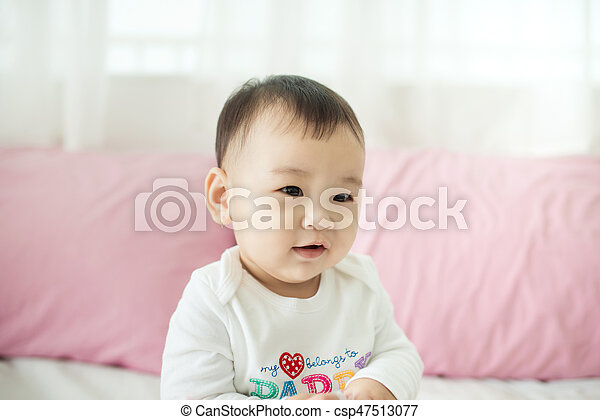 Sweet baby girl sitting on bed at home. - csp47513077