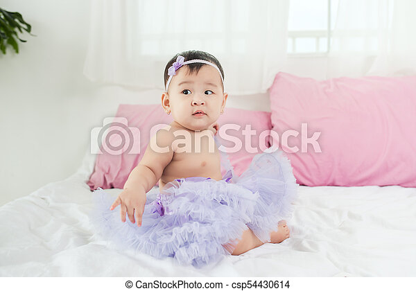 Sweet baby girl sitting on bed at home. - csp54430614