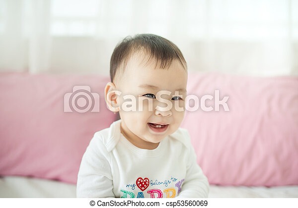 Sweet baby girl sitting on bed at home. - csp53560069