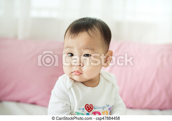 Sweet baby girl sitting on bed at home. - csp47884458