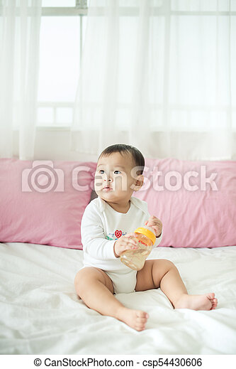 Sweet baby girl sitting on bed at home. - csp54430606