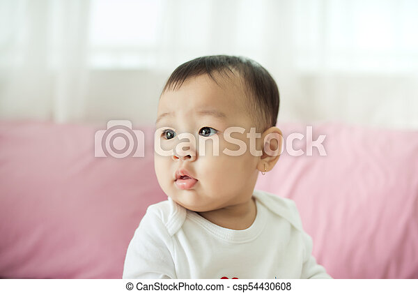 Sweet baby girl sitting on bed at home. - csp54430608