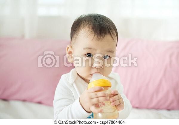 Sweet baby girl sucking milk in bottle at home. - csp47884464