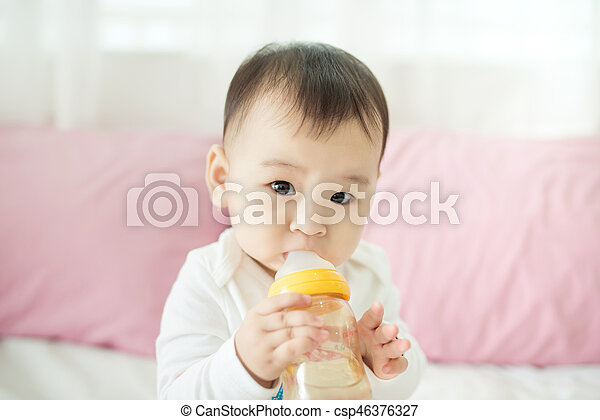 Sweet baby girl sucking milk in bottle at home. - csp46376327