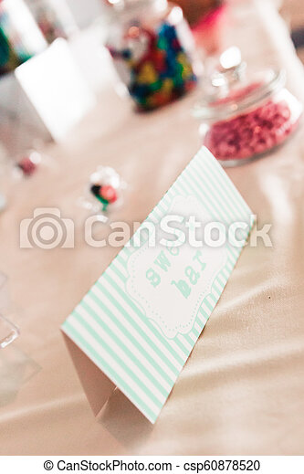 Sweet Bar Paper Sign on Wedding Table with Coloured Sweets - csp60878520
