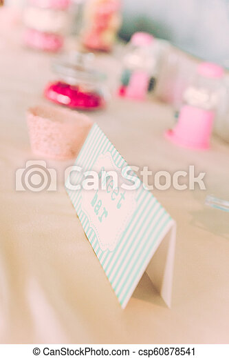 Sweet Bar Paper Sign on Wedding Table with Coloured Sweets - csp60878541