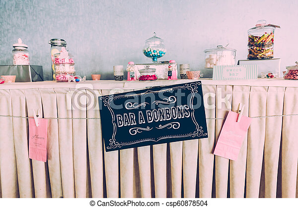Sweet Bar Paper Sign on Wedding Table with Coloured Sweets - csp60878504