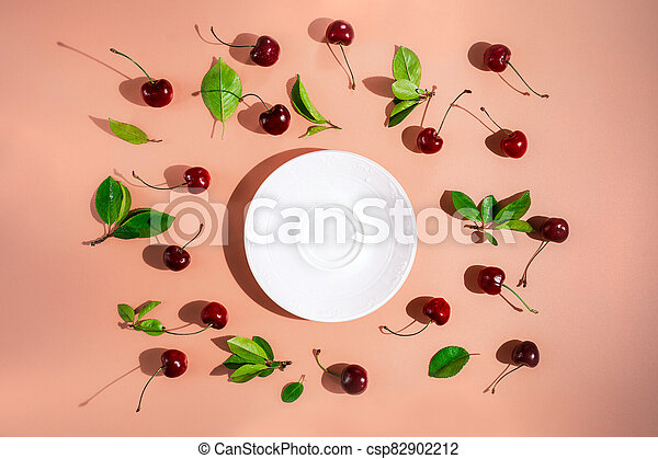 Sweet cherries with leaves surrounding empty white plate on pink colored background, top view - csp82902212