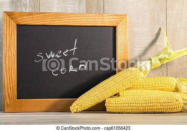 Sweet Corn with black desk as decoration for Thanksgiving Table, Halloween, and the Fall Season. Beautiful food art background - csp61056423
