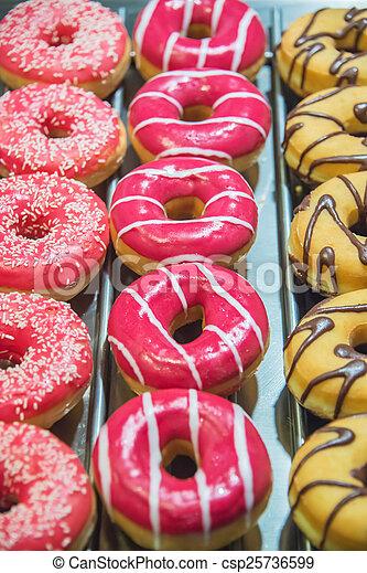 Sweet donuts arranged at display - csp25736599