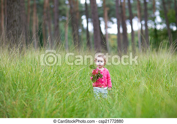 Sweet little baby girl walking in a autumn park playin - csp21772880