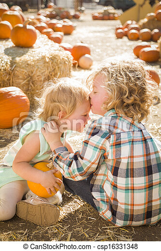 Sweet Little Boy Kisses His Baby Sister at Pumpkin Patch - csp16331348