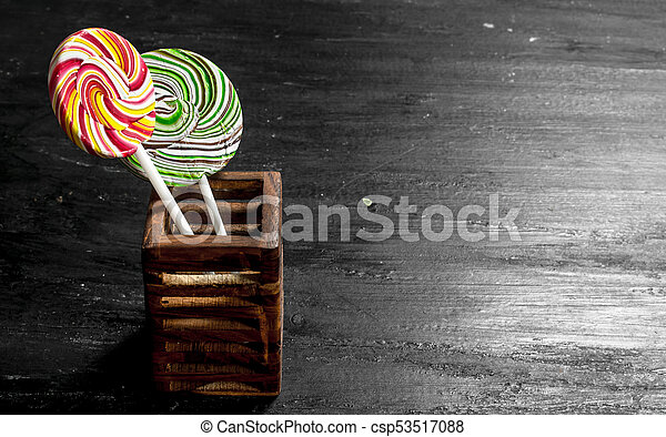 Sweet lollipops in a wooden stand. - csp53517088