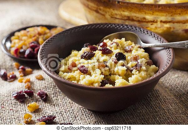 Sweet millet porridge with raisins and dried cranberries - csp63211718