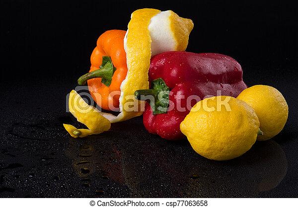 Sweet peppers and lemons in black studio. - csp77063658