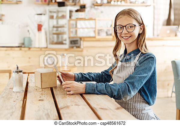 Sweet teenage girl familiarizing herself with a menu - csp48561672