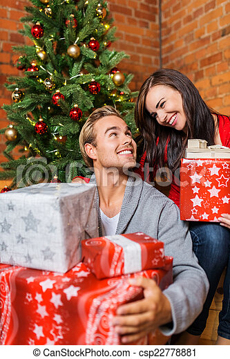 sweet young couple holding christmas gifts csp22778881