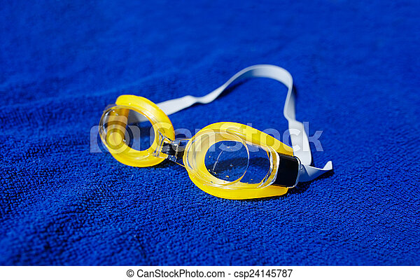 Swimming glasses at the towel. Shallow depth of field (dof). - csp24145787