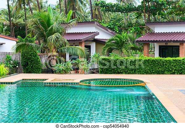 Swimming pool in a tropical hotel with palms and bungalows