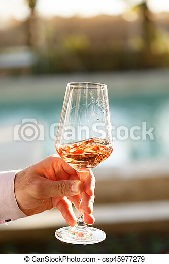 Swirling glass of rose wine at wine tasting. Concept of rose wine - csp45977279
