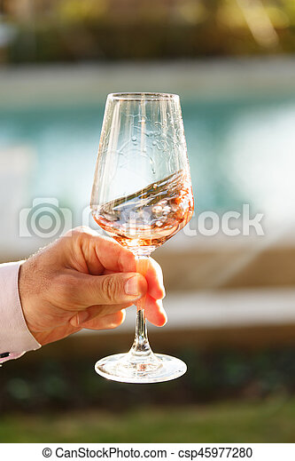 Swirling glass of rose wine at wine tasting. Concept of rose wine - csp45977280