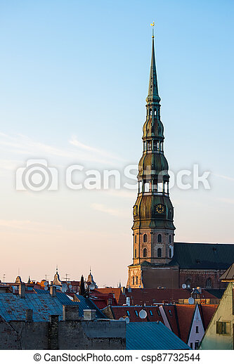 Symbol of Riga, old clock on medieval church tower among roofs ancient buildings with European architecture - csp87732544