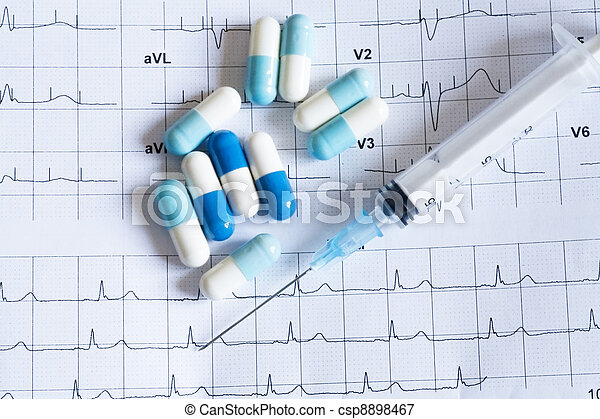 Syringe and tablets on the paper with graph of heart rhythm - csp8898467