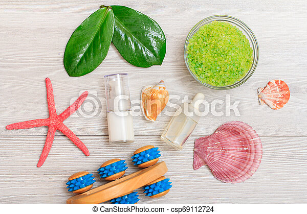 Syringe with eye cream, bottles with cream for face skin and aromatic oil, hand massager, bowl with sea salt on boards. - csp69112724