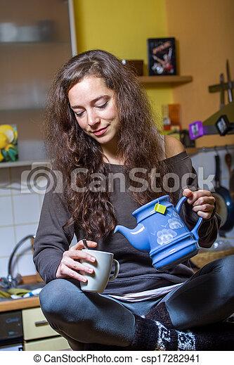 Una mujer bebiendo té en la cocina - csp17282941