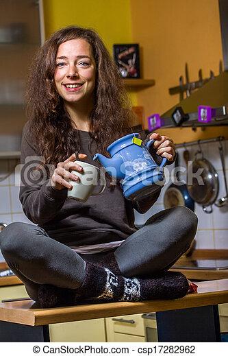 Una mujer bebiendo té en la cocina - csp17282962