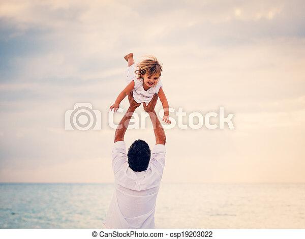 Vater und Tochter spielen bei Sonnenuntergang am Strand - csp19203022