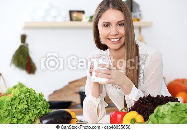 tabela, segurando, legumes, madeira, copo, sentando, enquanto, olhar, branca, câmera, mulher, verde, feliz, cozinha, jovem - csp48035656