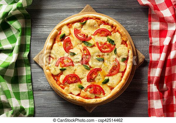 Pizza italiana en la mesa de madera - csp42514462