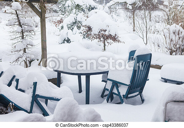 Table and chairs on a terrace in the winter covered with a lot of snow - csp43386037