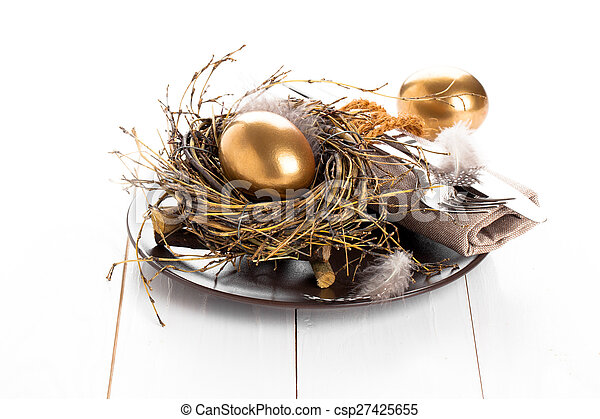 table decoration on white wooden background with Chicken golden egg - csp27425655