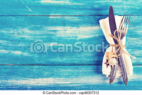 Table setting with a seaside theme. fork and knife, napkin, shells. Summer table setting in a nautical theme, with space for text, top view. Marine theme. napkin, cutlery and seashells on a blue background