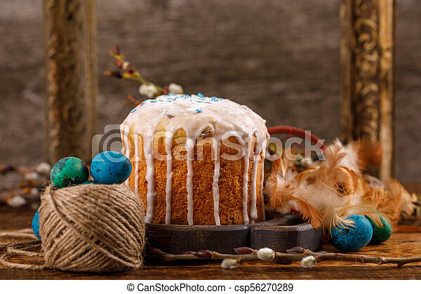 Table with Easter cakes and Easter eggs with willow branches. Easter still life with an ancient frame for a picture in the background. Easter in a rustic style. - csp56270289