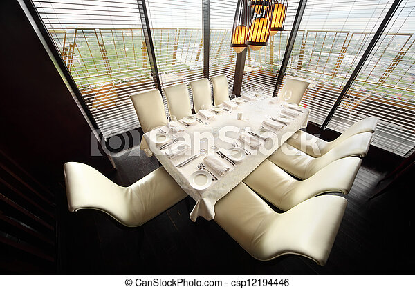 table with white tablecloth and serving and ten white chairs in empty lit restaurant - csp12194446