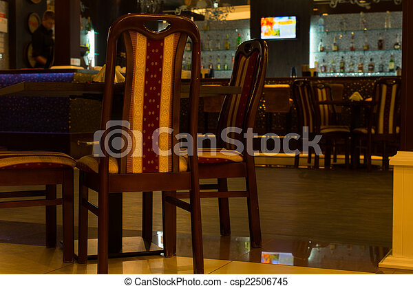 chairs and tables in empty bar room