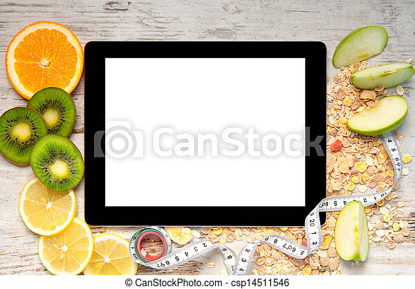 tablet computer on a wooden table with fruit and a measuring tape for weight loss and diets