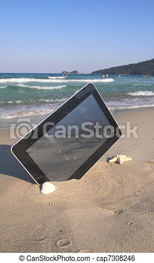 Tablet computer on the beach  - csp7308246