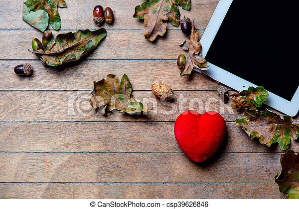 tablet, heart -shaped toy and fallen leaves - csp39626846
