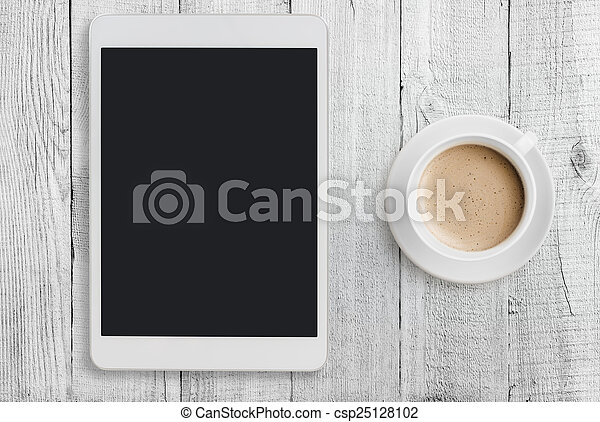 Tablet pc on table with coffee cup - csp25128102