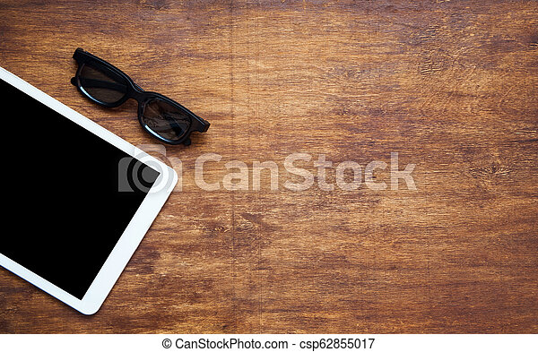 Tablet pc on wooden table with black glasses. View from the top. Copy space - csp62855017
