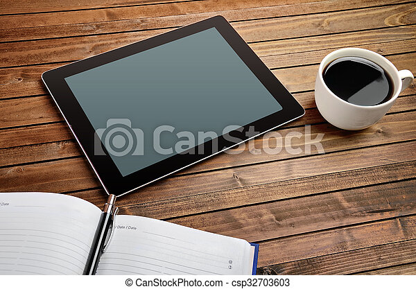 Tablet with coffee cup and notebook - csp32703603