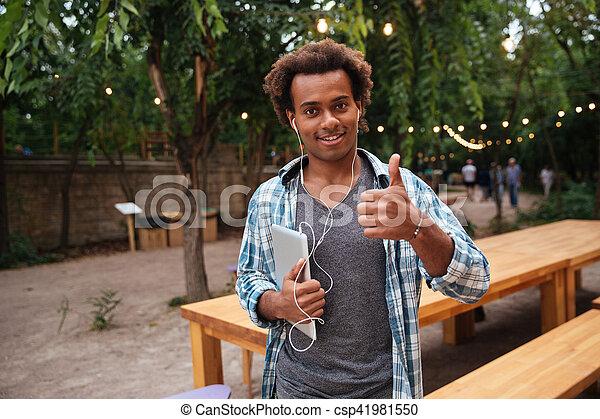 Un hombre feliz con auriculares sosteniendo tablet y mostrando pulgares arriba - csp41981550