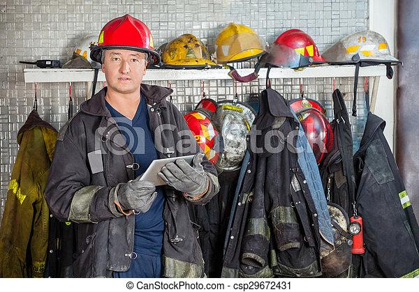Bombero sosteniendo tableta digital en la estación de bomberos - csp29672431